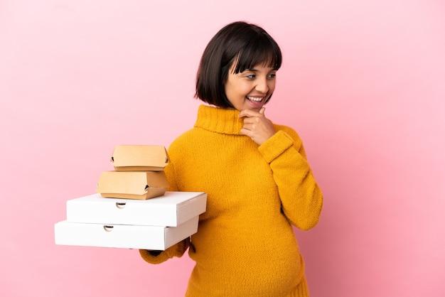 横を見て笑っているピンクの背景に分離されたピザやハンバーガーを保持している妊婦