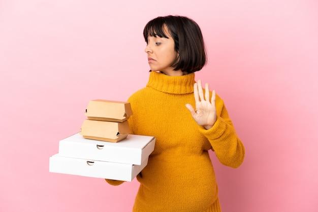 Беременная женщина, держащая пиццу и гамбургеры на розовом фоне, делая жест стоп и разочарованная