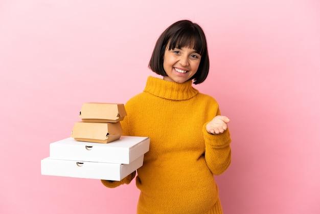 Беременная женщина, держащая пиццу и гамбургеры на розовом фоне, пожимая руку для закрытия хорошей сделки
