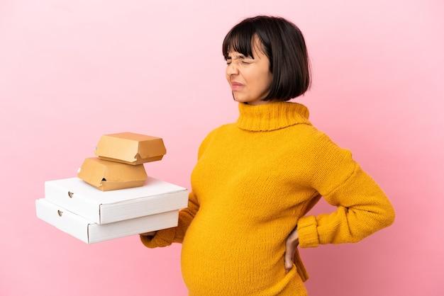 Беременная женщина, держащая пиццу и гамбургеры, изолированные на розовом фоне, страдает от боли в спине из-за того, что приложила усилия