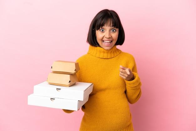 ピンクの背景に分離されたピザやハンバーガーを保持している妊婦は驚いて正面を指しています