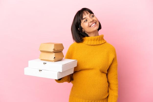 見上げながらアイデアを考えてピンクの背景に分離されたピザやハンバーガーを保持している妊婦