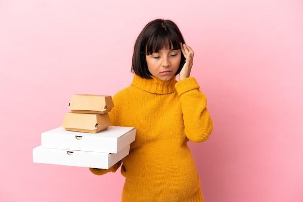 두통이 있는 분홍색 배경에 격리된 피자와 햄버거를 들고 있는 임산부
