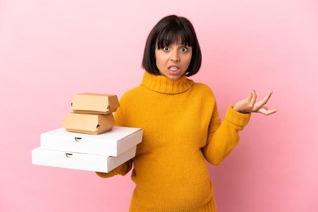 Беременная женщина, держащая пиццу и гамбургеры на розовом фоне с шокированным выражением лица