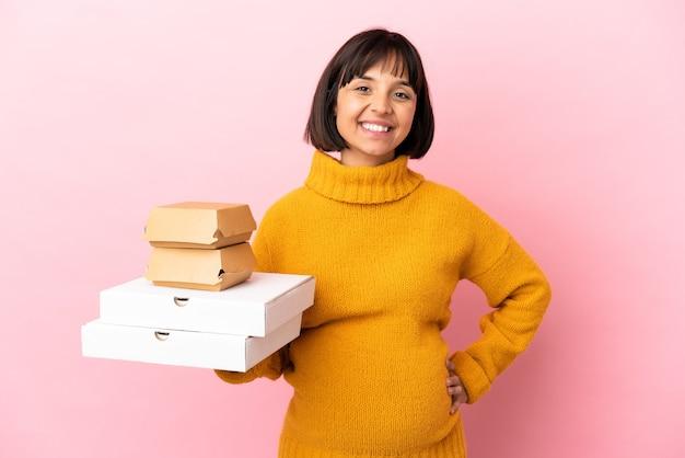 피자와 햄버거를 들고 임신 한 여자는 엉덩이에 팔을 들고 웃고 분홍색 벽에 고립 된