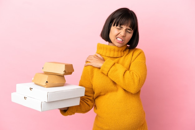Pregnant woman holding pizzas and burgers isolated on pink background suffering from pain in shoulder for having made an effort