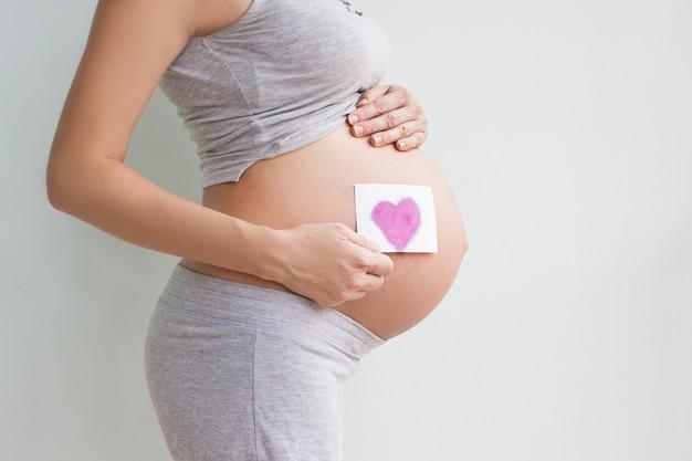 新しい人生の象徴、彼女の腹に赤いハートと手を保持している妊婦