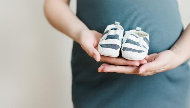 Беременная женщина держит обувь для новорожденного