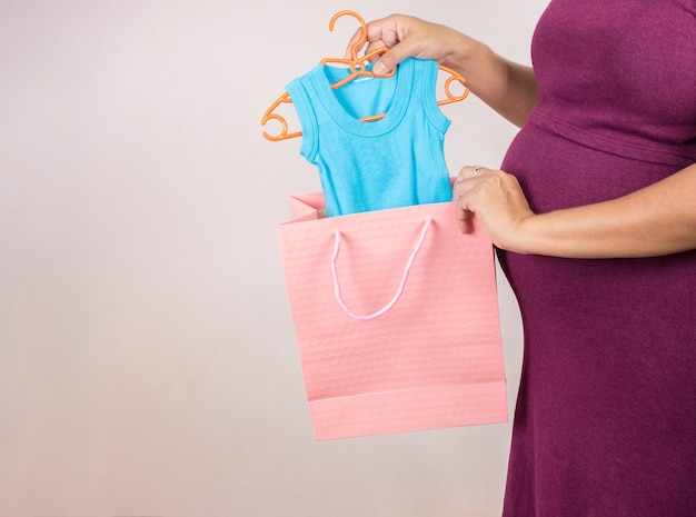 Pregnant woman holding shoping bags in superstore