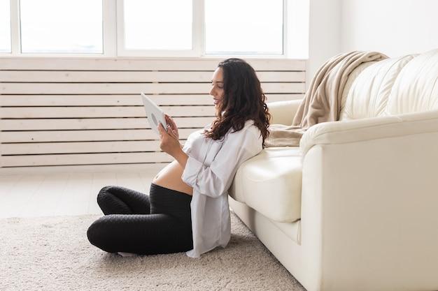 Беременная женщина, держащая планшет, сидит на ковре возле дивана в гостиной дома