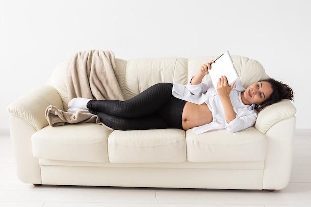 Беременная женщина, держащая планшет, сидя на ковре возле дивана в гостиной дома.