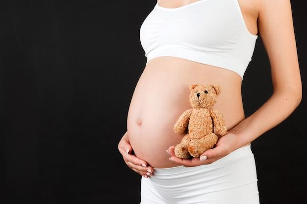 검은 바탕에 테 디 베어를 들고 임신 한 여자
