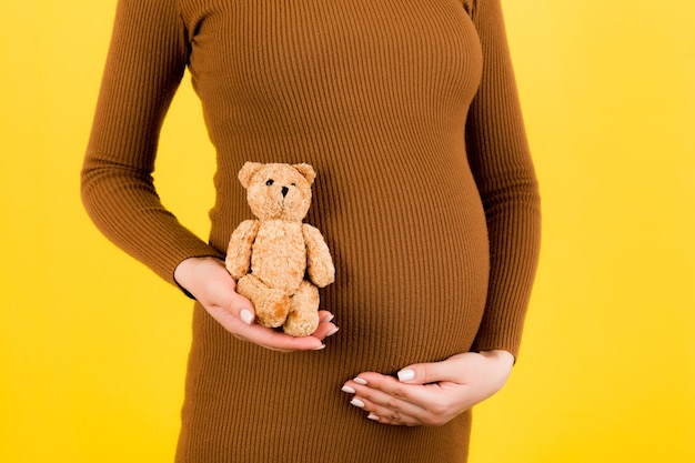 Pregnant woman holding teddy bear and touching her belly