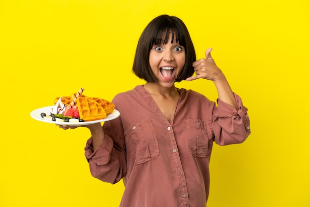 Pregnant woman holding waffles isolated on yellow background making phone gesture. call me back sign