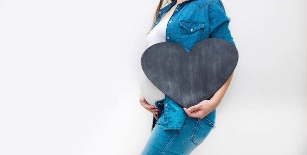 妊娠中の女性は黒い心を持っています。妊娠、親子関係、準備と期待の概念。閉じる