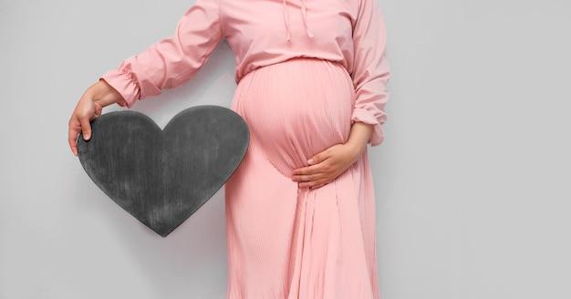 Беременная женщина держит пустую доску шаблона для вашего текста.