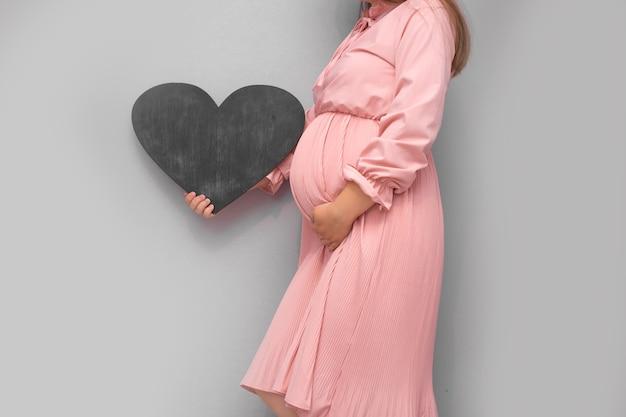 妊娠中の女性はあなたのテキストの空のテンプレートホワイトボードを保持しています。
