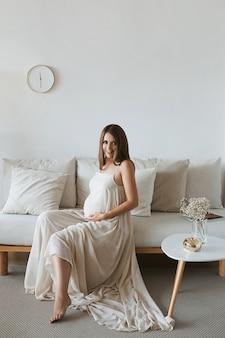Беременная женщина держит живот за руку, сидя на диване в уютном домашнем интерьере