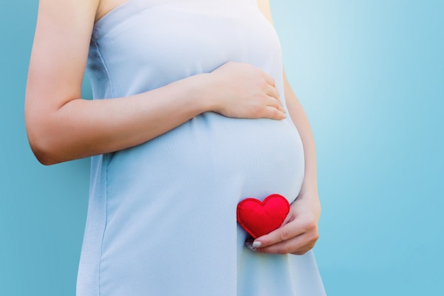 A pregnant woman holds in her hand a red heart on blue