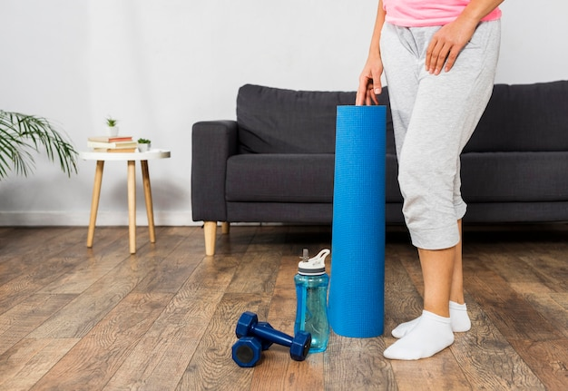 Pregnant woman at home with water bottle and weights