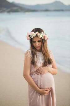바다에 아름 다운 드레스에 임신 한 여자.