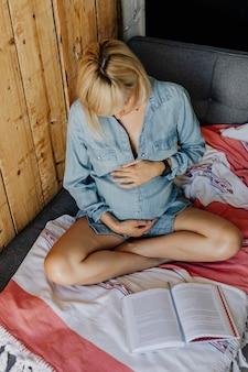 ソファで本を読んでいるデニムのドレスを着た妊婦