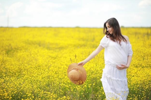 Беременная женщина в платье в поле цветов