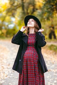 Беременная женщина в осеннем парке.