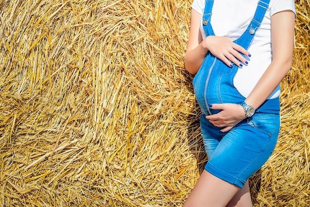 Беременная женщина в синем джинсовом комбинезоне держит животик на желтом фоне стога сена, крупным планом, копией пространства