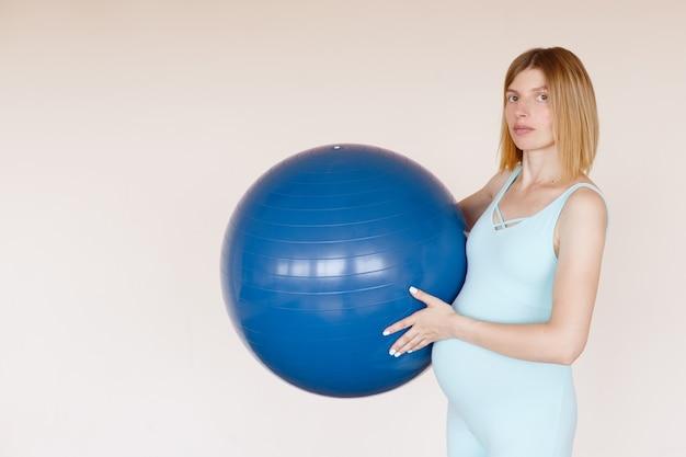 トレーニング中のフィットネスボールと青いジャンプスーツの妊娠中の女性
