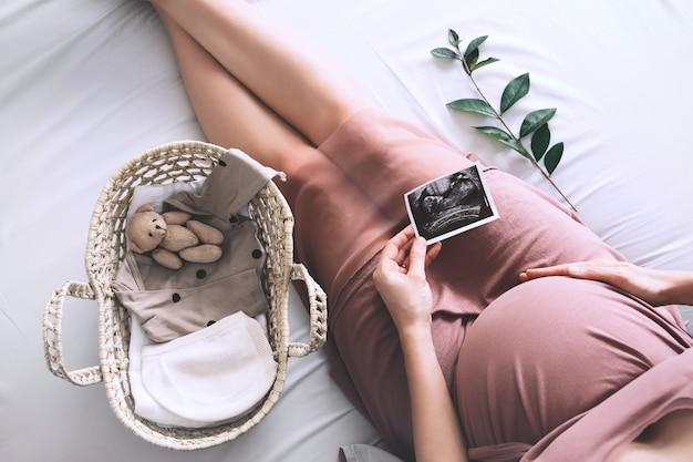 赤ちゃんの誕生を待っている超音波画像妊婦とドレスを着た妊婦