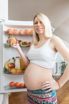 開いた冷蔵庫の前の妊娠中の女性