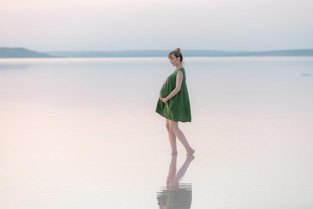 ビーチでポーズをとって緑のドレスを着た妊婦。リラックスして自然の中での生活を楽しんでいる若い幸せな妊婦