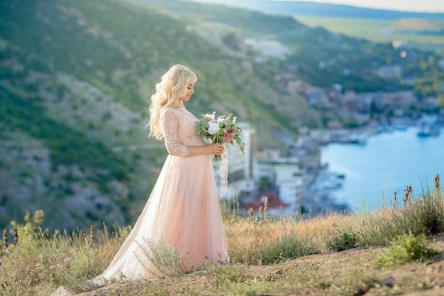 Беременная женщина в природе. мать красивой женщины будущая в белом длинном платье outdoors