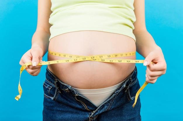줄자로 그녀의 배꼽을 측정 열린 청바지에 임신 한 여자