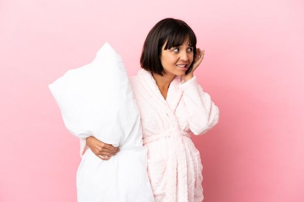 Беременная женщина в пижаме на розовом фоне разочарована и закрывает уши