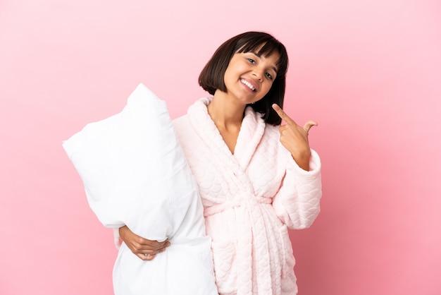 Беременная женщина в пижаме, изолированные на розовом фоне, показывает палец вверх