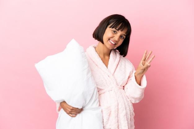 幸せなピンクの背景に分離されたパジャマの妊娠中の女性と指で3を数える