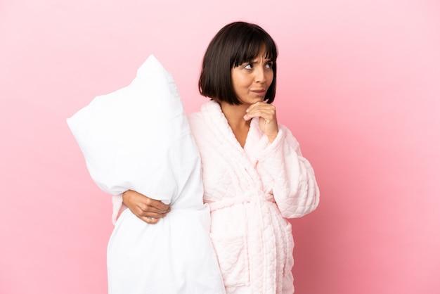 疑いと思考を持っているピンクの背景に分離されたパジャマの妊娠中の女性