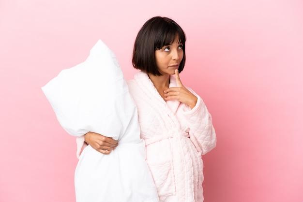 見上げている間疑いを持っているピンクの背景に分離されたパジャマの妊娠中の女性