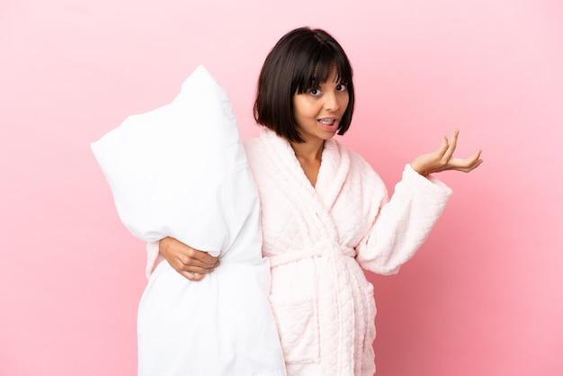 手を上げている間疑いを持っているピンクの背景に分離されたパジャマの妊娠中の女性