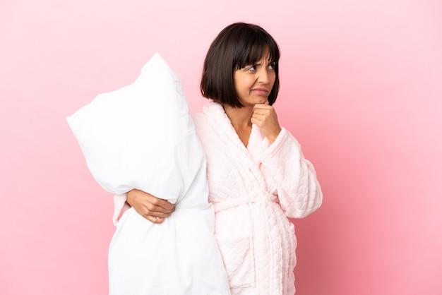 疑いを持っているピンクの背景に分離されたパジャマの妊娠中の女性