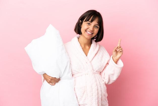 素晴らしいアイデアを指しているピンクの背景に分離されたパジャマの妊娠中の女性