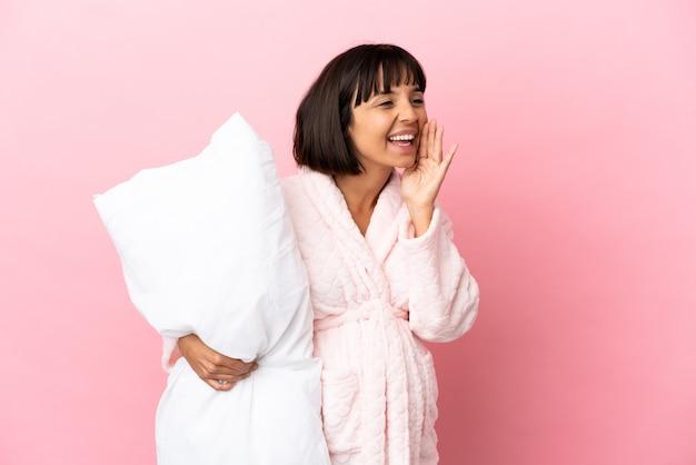ピンクの背景に分離されたパジャマを着た妊婦が口を大きく開いて叫んでいる