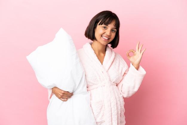 ピンクの背景で隔離のパジャマを着た妊婦が指でokサインを示しています