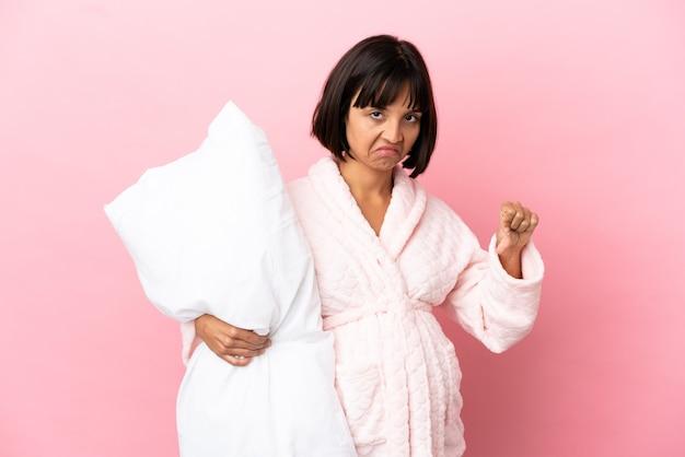 부정적인 표정으로 엄지손가락을 아래로 보여주는 분홍색 배경에 고립 잠옷에 임신한 여자