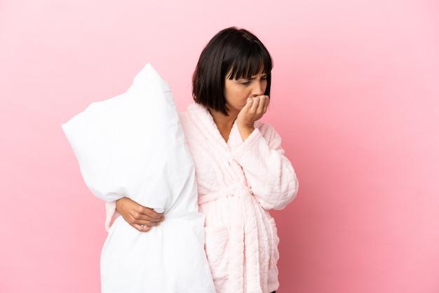疑いを持っているピンクの表面に分離されたパジャマの妊娠中の女性