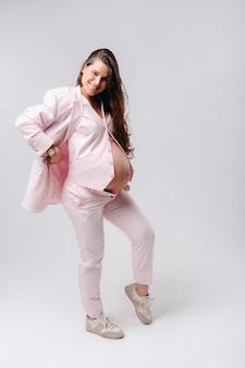 灰色の背景にピンクのスーツのクローズアップで妊娠中の女性。