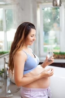Беременная женщина в спортивной домашней одежде держит витамин и стакан воды. забота о здоровье во время беременности. утренняя рутина. фото высокого качества