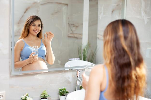 Беременная женщина в спортивной домашней одежде держит витамин и стакан воды. забота о здоровье во время беременности. утренняя рутина. отражение в зеркале. фото высокого качества